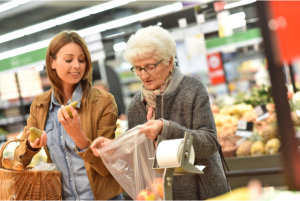 caregiver assisting her patient in buying fruits